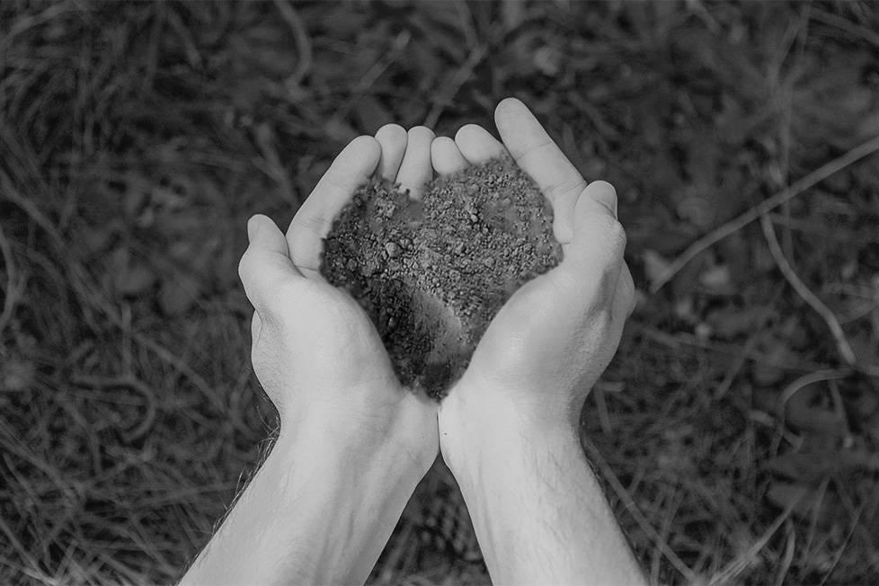 człowiek trzymający ziemię w dłoniach
